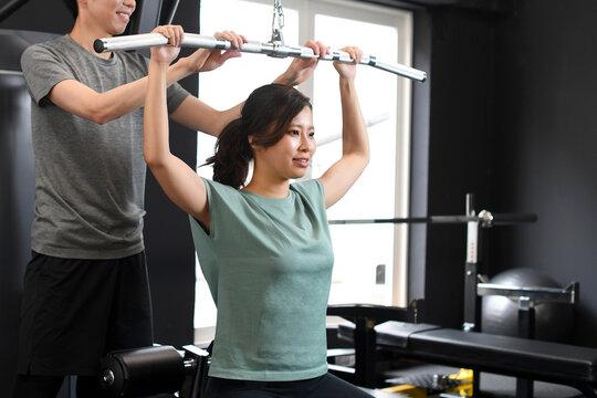 ラットプルダウンをするアジア人女性と補助をする男性トレーナー