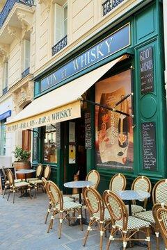 """Devanture d'un bar à vin / caviste """"Vin et Whisky"""" à Paris, avec des tables et des chaises sur la terrasse du bistrot – mai 2021 (France)"""