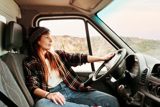 Woman sitting in van in mountains