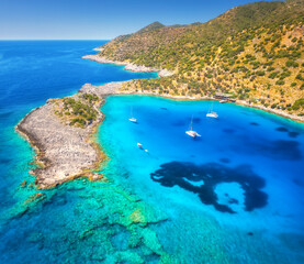 Aerial view of beautiful yachts and boats on the sea at sunset in summer. Akvaryum koyu in Turkey. Top view of luxury yachts, sailboats, clear blue water, rock, sky, mountain and green trees. Travel