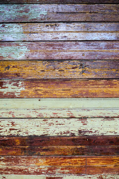 Texture, old rustic paint-striped wood slatted wall covered with peeling paint.