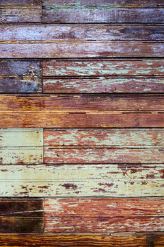 Texture, old grungy paint-striped wood slatted wall covered with peeling paint.