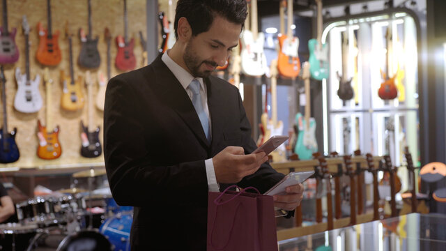 An upwardly mobile Muslim man using smart payment to pay for a product at a sale terminal with nfc identification payment for verification and authentication