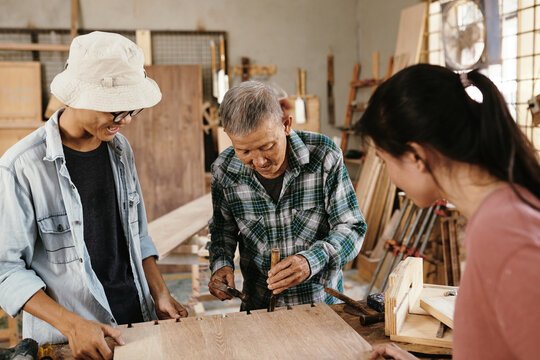 Young people watching experienced elderly carpenter using chisel and hammer when making cuts in wooden board to fit in butterfly inlay keys
