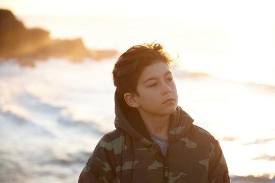 Young boy wearing camo jacket on sunrise