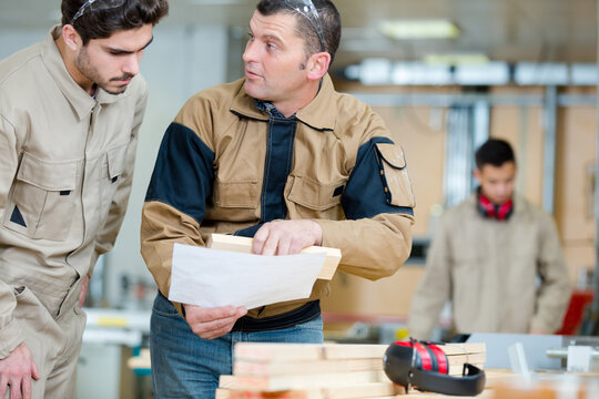 carpentry workers talking holding small plank of industrial wood
