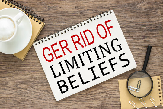 Get Rid Of Limiting Beliefs. text on wood table, on white paper