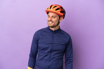 Fototapeta Young Brazilian cyclist man isolated on purple background looking to the side and smiling obraz