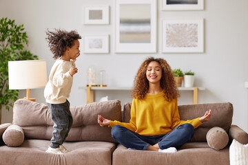 Fototapeta Young african woman mother in lotus pose meditating while child playing nearby in living room obraz