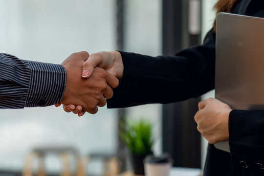Close up of Businessman and woman shake hands as hello in office,Friend welcome, introduction, greet or thanks gesture, product advertisement, partnership approval, arm, strike a bargain on deal conc