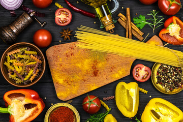 Fototapeta An assortment of fresh vegetables and spices, olive oil, cutting board and pasta on a black background with space for text. obraz