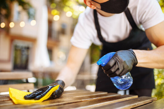 A waiter in a black protective mask wipes tables with a disinfectant before opening. Dust cleaning agent. Wipes the table with a rag in a restaurant.