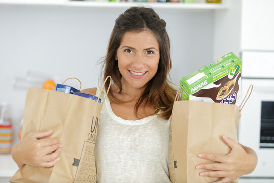 portrait of beautiful young woman holding grocery shopping bags