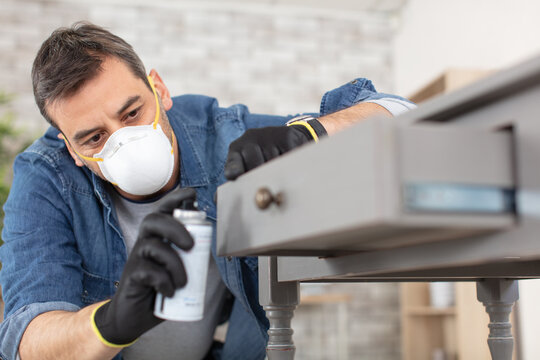 man painting desk at home with spray paint