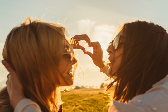 Female best friends stacking hands in heart gesture