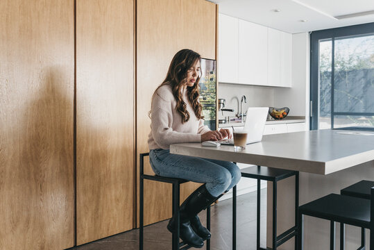 Woman working on laptop in kitchen at home