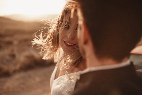 Anonymous groom embracing bride in countryside