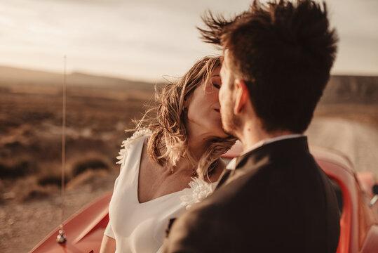 Newlyweds kissing near sports car in desert