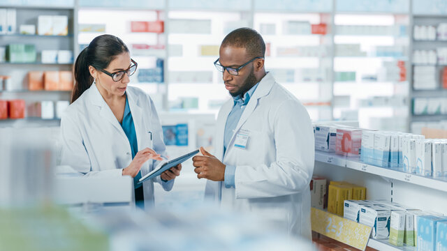 Pharmacy: Black Male and Caucasian Female Pharmacists Use Digital Tablet Computer Talk about Medicine, Drugs, Vitamins, Supplements, Vaccine, Health Care Products. Medical Professionals in Drugstore