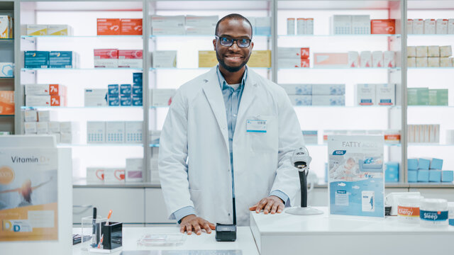 Pharmacy Drugstore Checkout Counter: Portrait of Handsome Professional Black Male Pharmacist Wearing White Lab Coat, Looks at Camera, Smiles. Shelves with Medicine Packages, Health Care Products