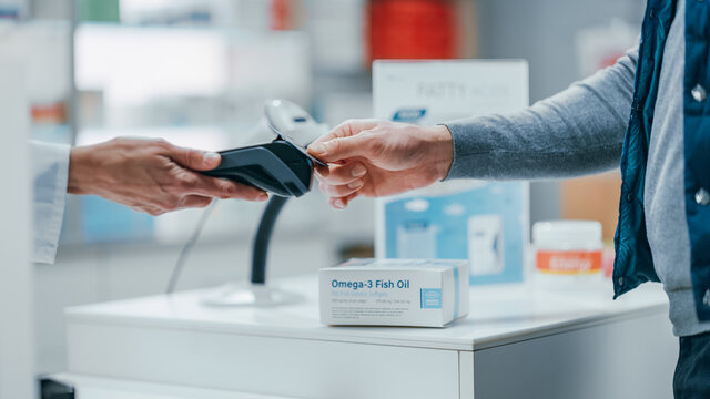 Pharmacy Drugstore Checkout Cashier Counter: Pharmacist and a Customer Using Contactless Credit Card with Payment Terminal to Buy Prescription Medicine, Health Care Goods. Close-up Focus on Hands