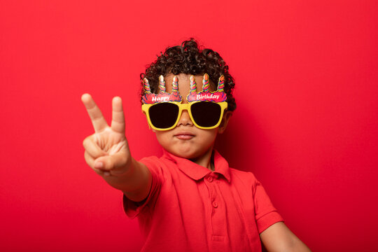 Cool boy in birthday glasses on red background