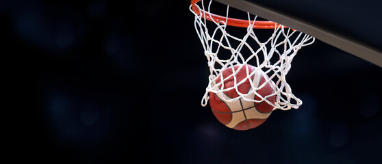 The orange basketball ball flies through the basket. Professional sport concept..