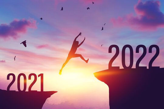 Silhouette man jumping between cliff with number 2021 to 2022 and birds flying at top of mountain. Freedom challenge and travel adventure holiday concept.