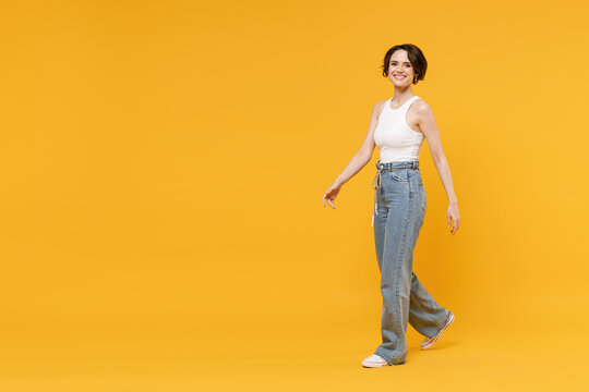 Full length side view young smiling happy woman 20s with bob haircut wear white tank top shirt walking going look camera isolated on yellow color background studio portrait People lifestyle concept