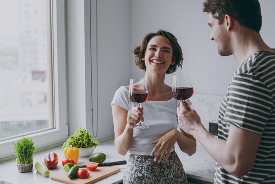 Young cheerful fun happy couple two woman man 20s in casual t-shirt clothes drink red wine celebrate new dwelling talking cooking food in light kitchen at home together Healthy diet lifestyle concept