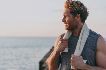 Fototapeta Close up young strong sporty athletic toned fit sportsman man 20s in sports clothes towel warm up training look aside at sunrise sun dawn over sea beach outdoor on pier seaside in summer day morning obraz