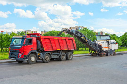 Road cold milling machine removes the old asphalt and loading into a dump truck. Repair of asphalt pavement of the road.