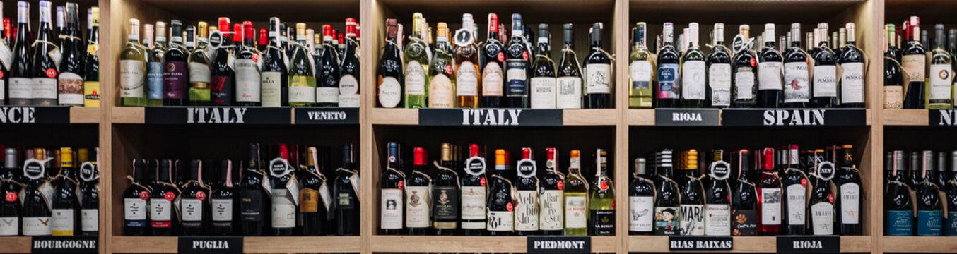 Minsk, Belarus - Juny 27, 2021: Various wine bottles sale on the wooden shelf in a supermarket shop.