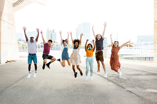 Happy multiracial people jumping together outdoors - Friendship concept with group of young friends from diverse cultures and races having fun with city background