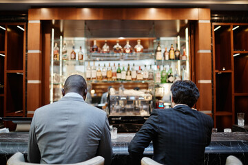 Obraz Back view portrait of two successful business people at bar in hotel lobby during business trip - fototapety do salonu