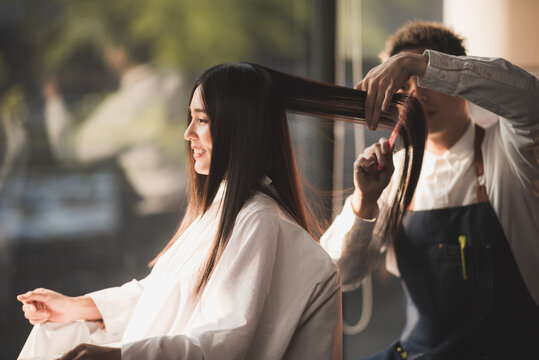 Asian long black straight  hair female cutting her hair at luxery salon with professional  dresser with scissor tool.