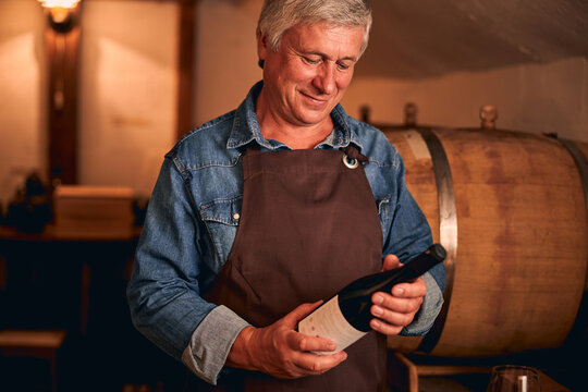 Handsome man in apron holding bottle of wine