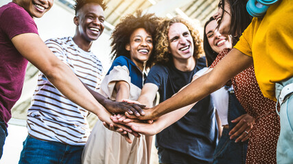 Fototapeta Multiracial happy young people stacking hands outside - Diverse friends unity togetherness in volunteer community - Concept about university, relationship, creative, youth and human resources obraz