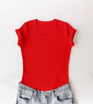 Red feminine t-shirt with jeans above white background. Mock up flat lay in minimalist style.
