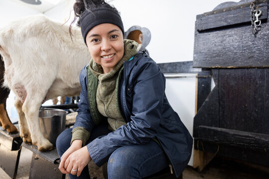 Portrait happy confident female farmer milking goat in barn
