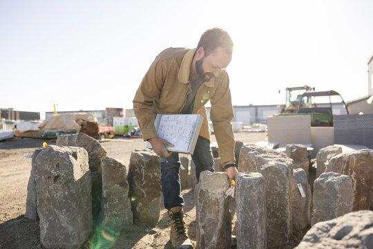 Worker looking at limestone rocks in industrial yard