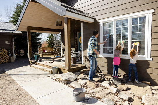 Rear view of father and daughters cleaning windows in front porch
