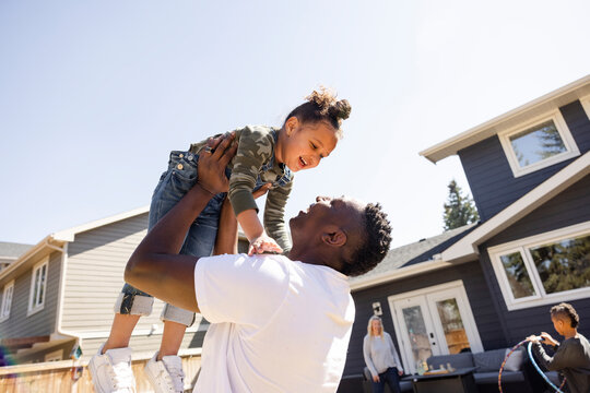 Portrait of father lifting daughter up in air in backyard