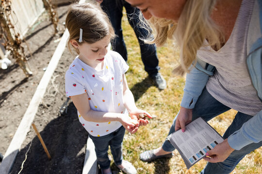 Girl showing plant bulbs in palms to mother in backyard