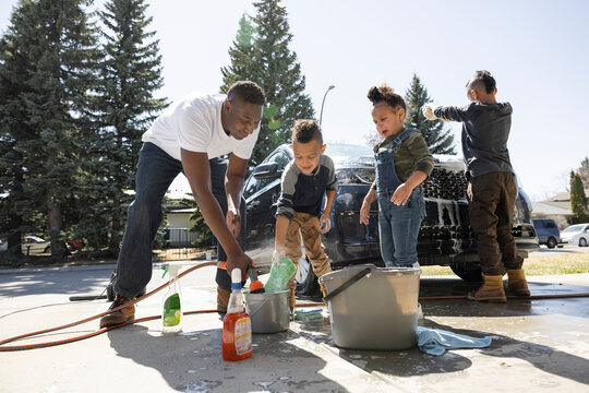 Father and children filling bucket with water in driveway