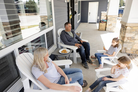 Family relaxing cookies at teatime on porch