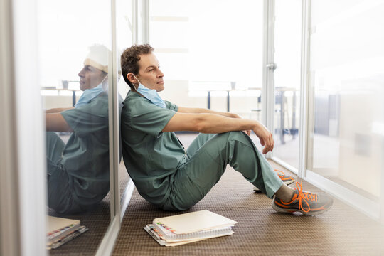 Tired male doctor resting in clinic corridor