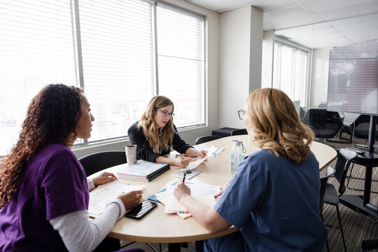 Female doctor and nurses discussing medical records in clinic