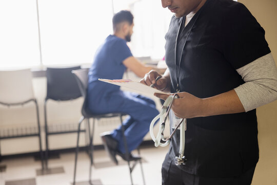 Male doctor reviewing medical chart in clinic