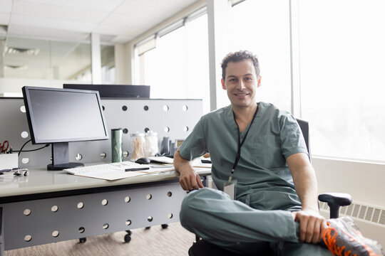 Portrait smiling handsome male doctor at desk in clinic office